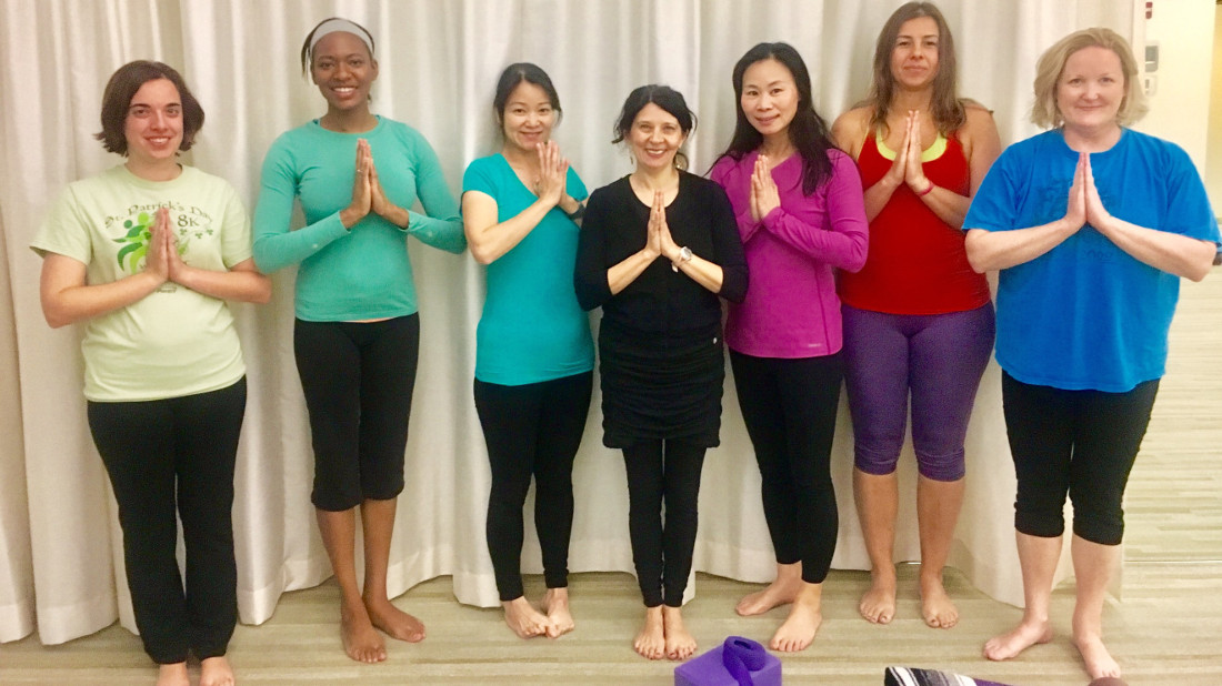 Employees gather after weekly yoga class, one of 15 wellness classes at APA